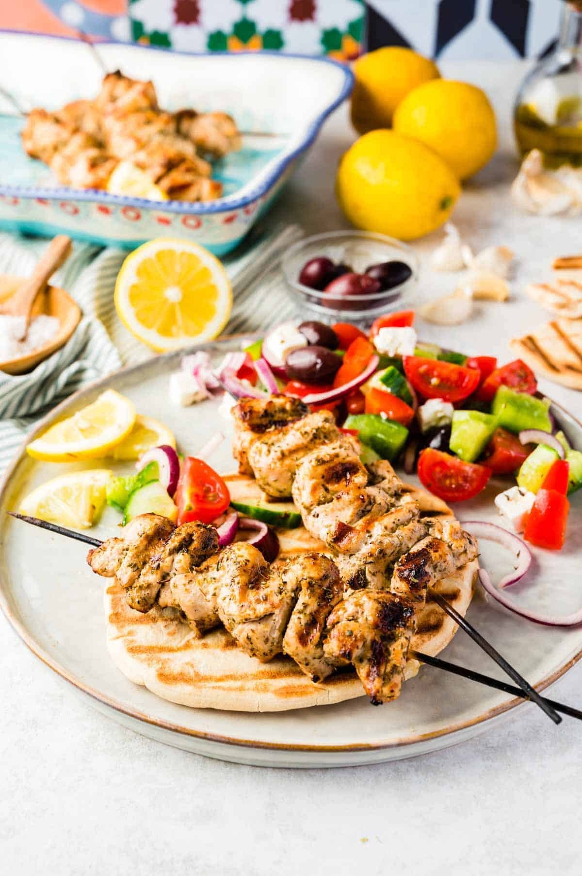 A Plate of Chicken Souvlaki, Grilled Bread and Greek Salad on a Cluttered Countertop