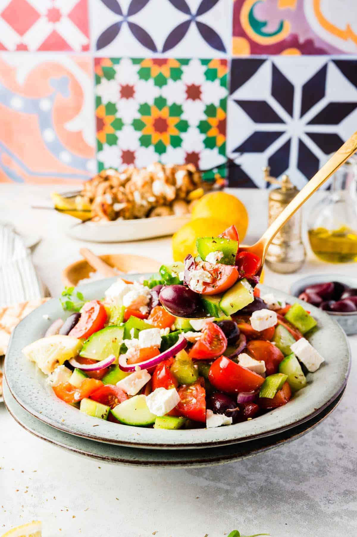 A Golden Spoon Lifting a Bite of Greek Salad From a Large Bowl