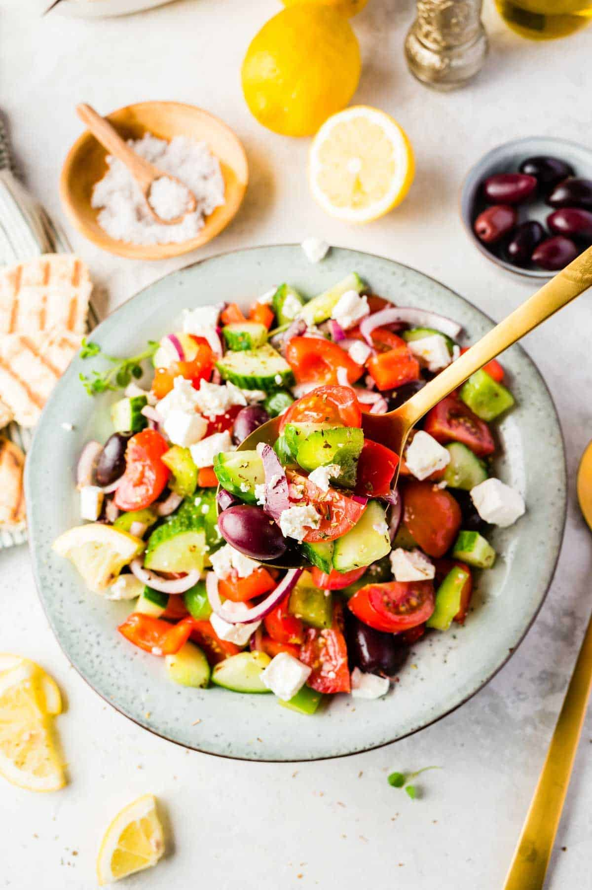 An Overhead Shot of a Freshly Made Greek Salad with Lemons and Kalamata Olived Behind it
