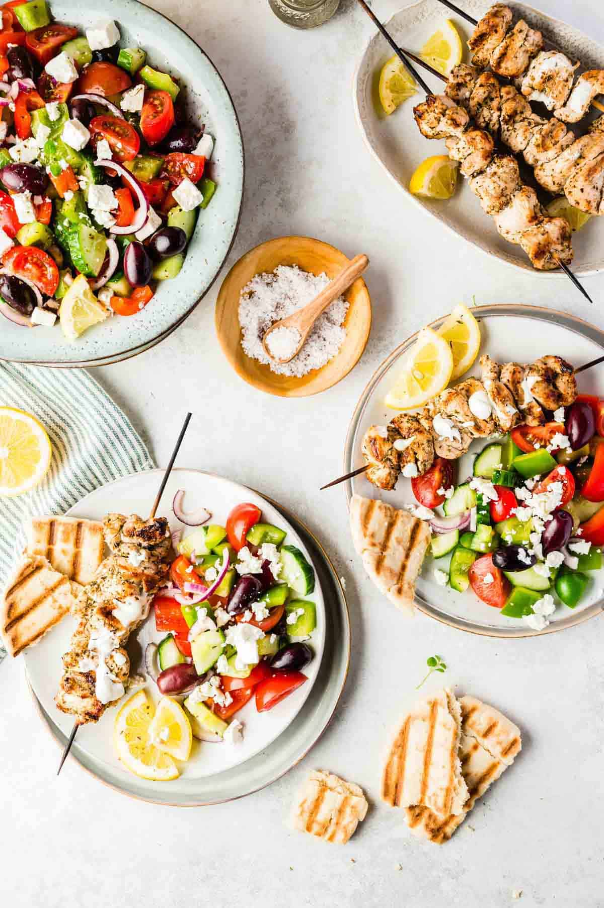 Two Helpings of Greek Salad, Chicken Kebabs and Grilled Bread Beside a Full Serving Bowl and Platter