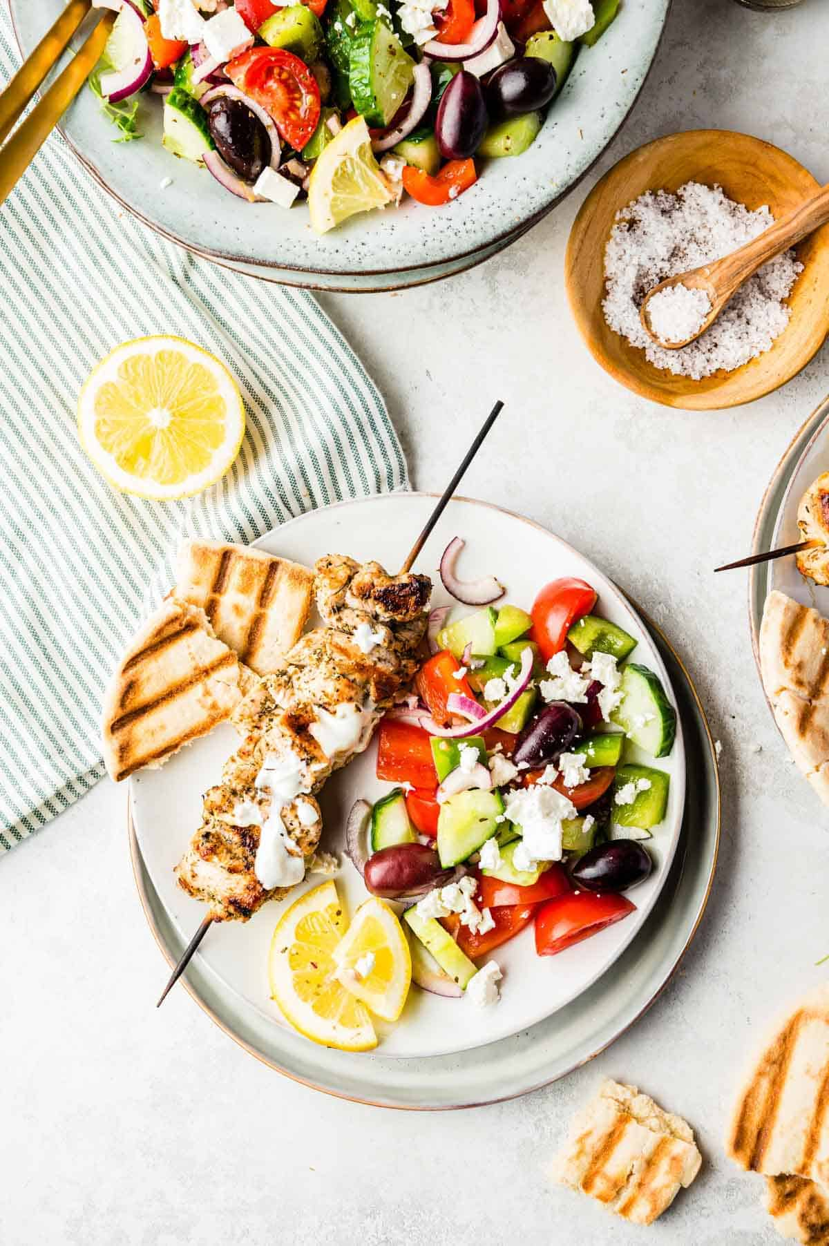 A Side Serving of Greek Salad on a Plate with Bread and Grilled Chicken