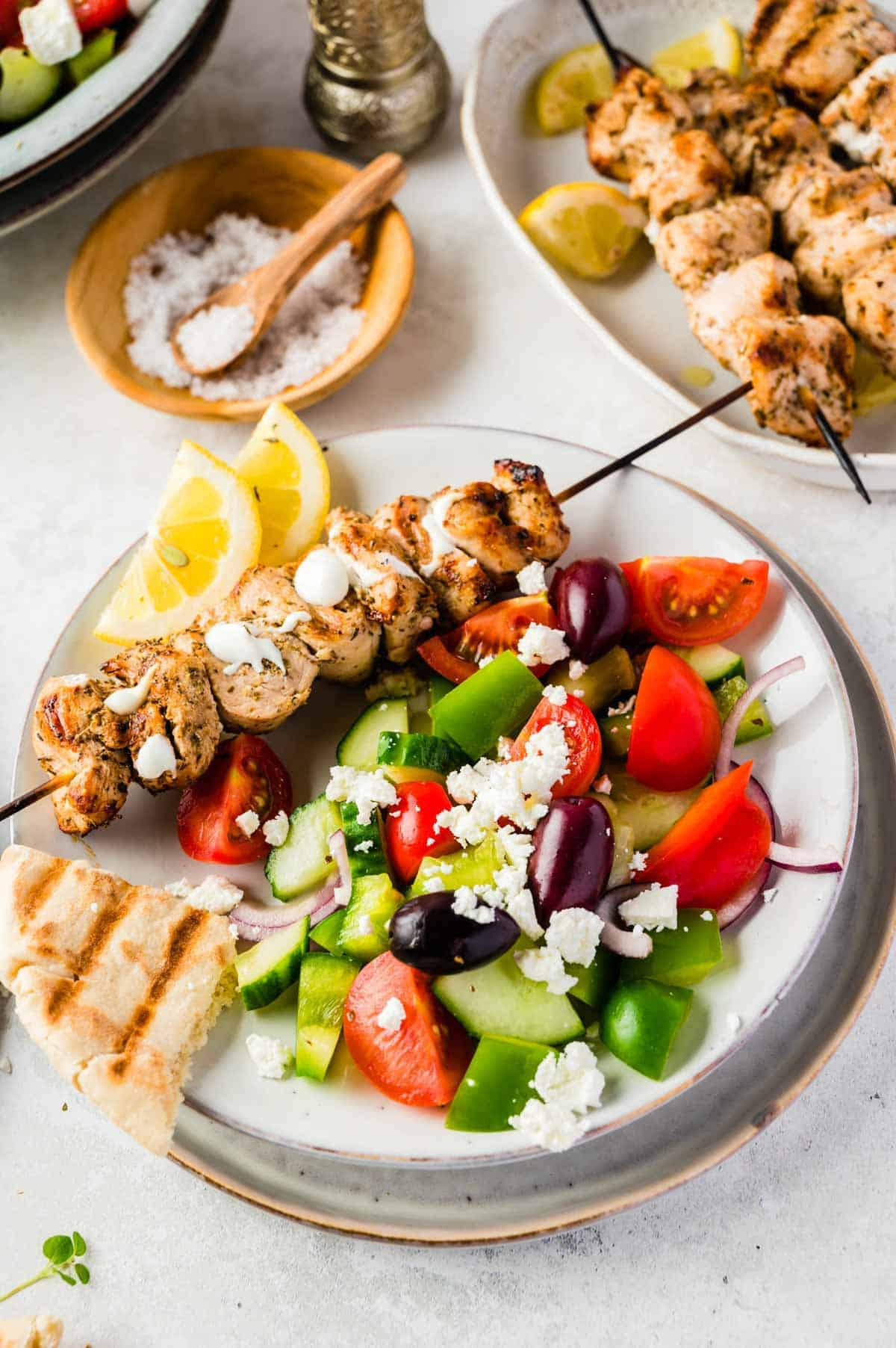 A Plate of Chicken Skewers, Pita Bread and Greek Salad Beside a Small Dish of Coarse Salt