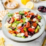 Two Doubled-Up Bowls Containing Greek Salad with Pita Bread and Spoons Beside Them