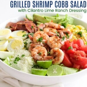 shrimp cobb salad in a bowl with eggs, bacon, tomatoes, corn, avocado, grated cheese, and limes