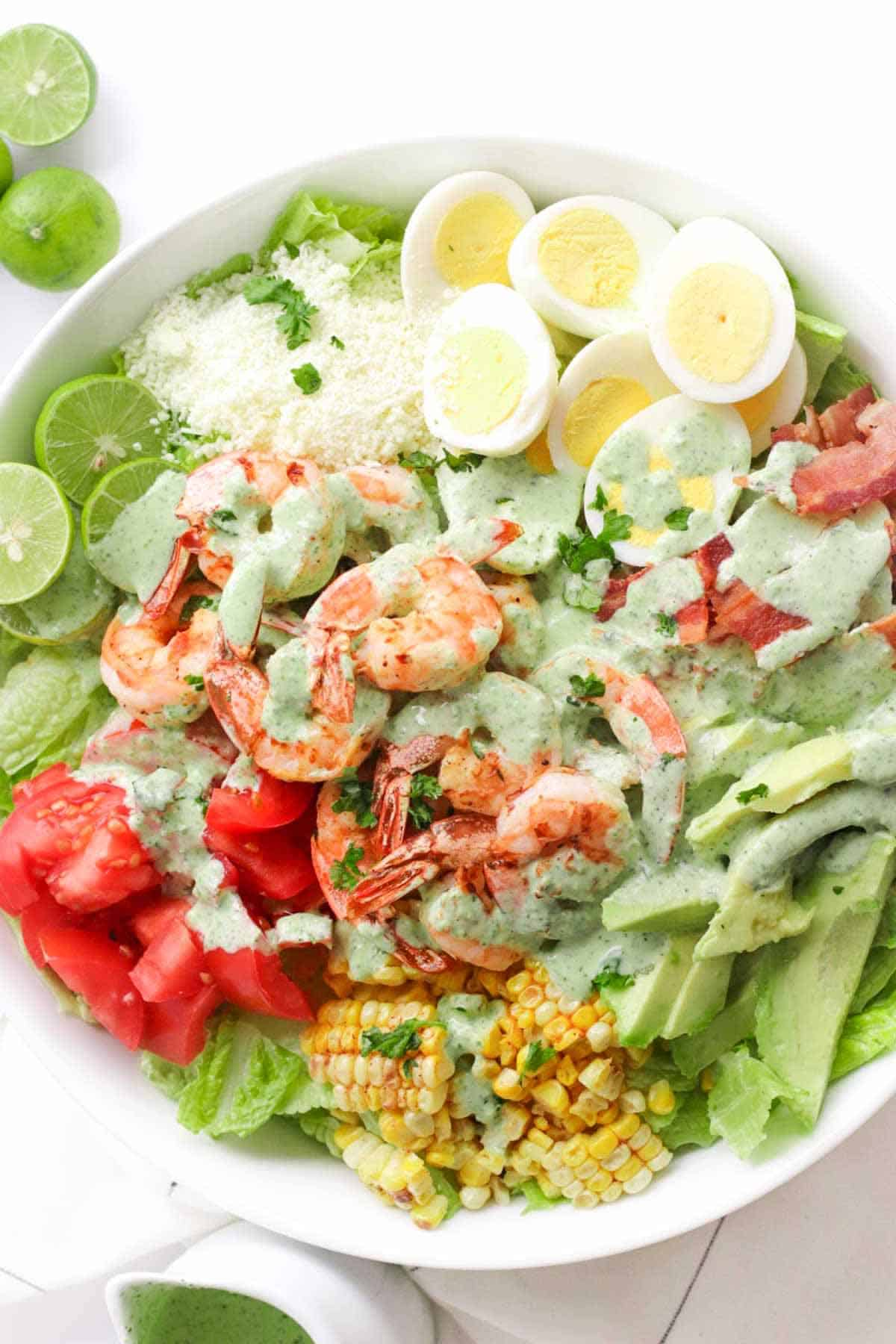 Shrimp Cobb Salad with hard boiled eggs, bacon, limes, tomatoes, avocado, cotija cheese, grilled corn, and cilantro lime dressing in a white serving bowl