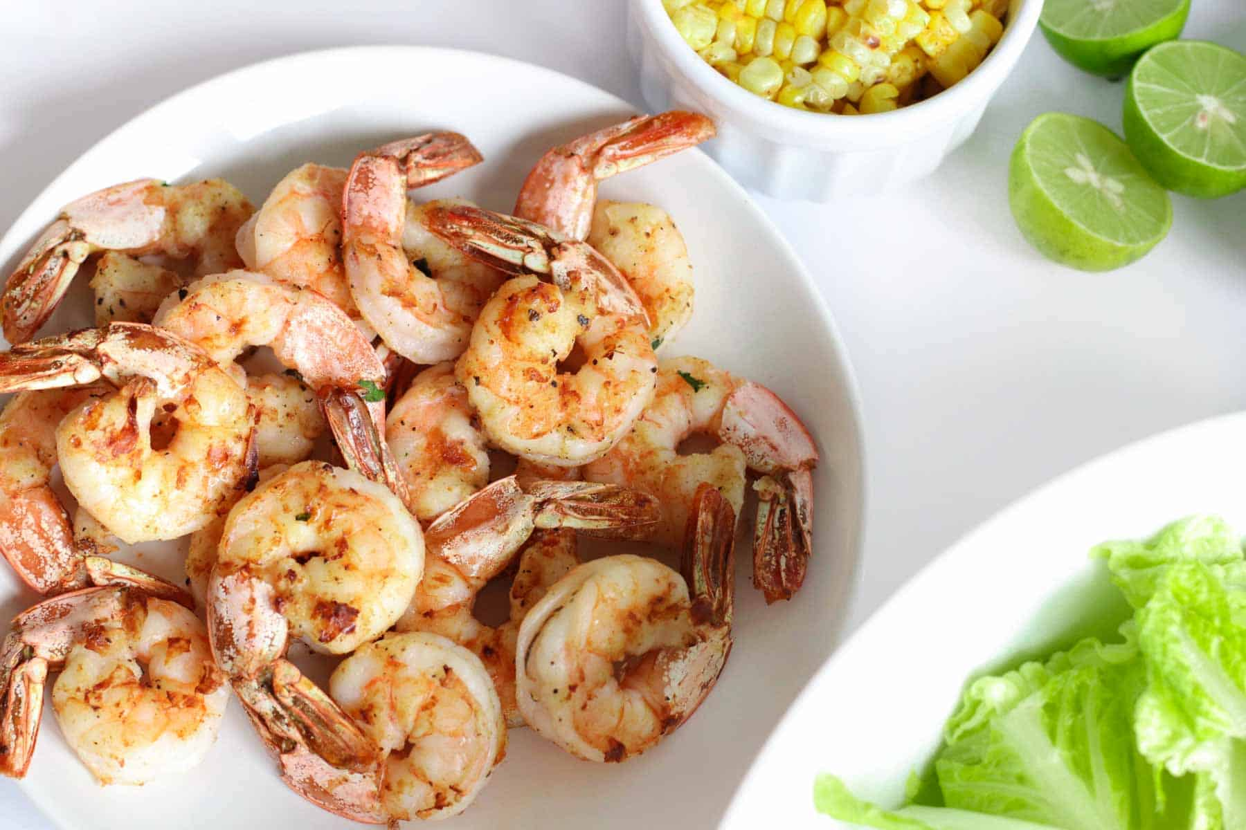 grilled shrimp in a bowl next to a small bowl with the grilled corn cut off the cob
