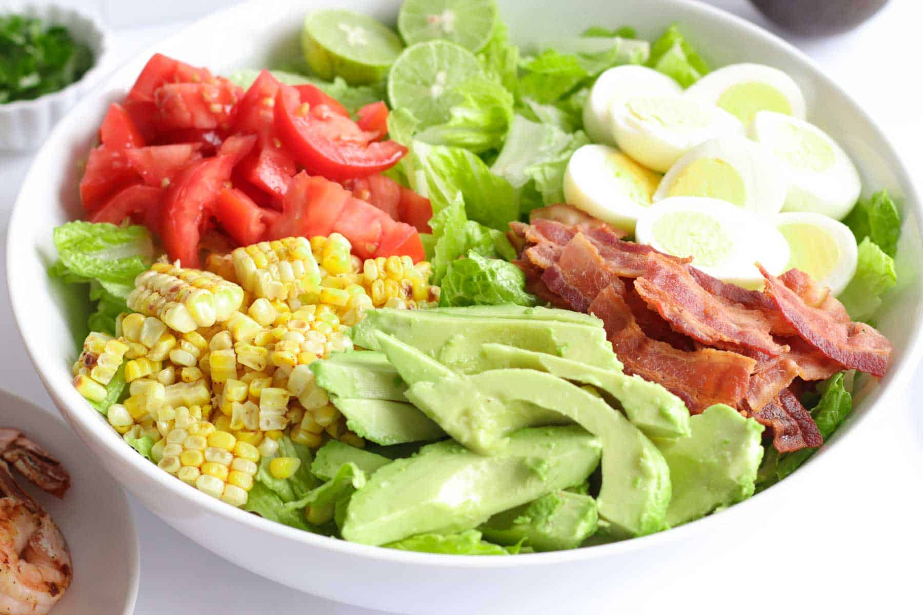 bowl of romaine lettuce topped with avocado, grilled corn, tomatoes, limes, ahrd boiled egg halves, and bacon