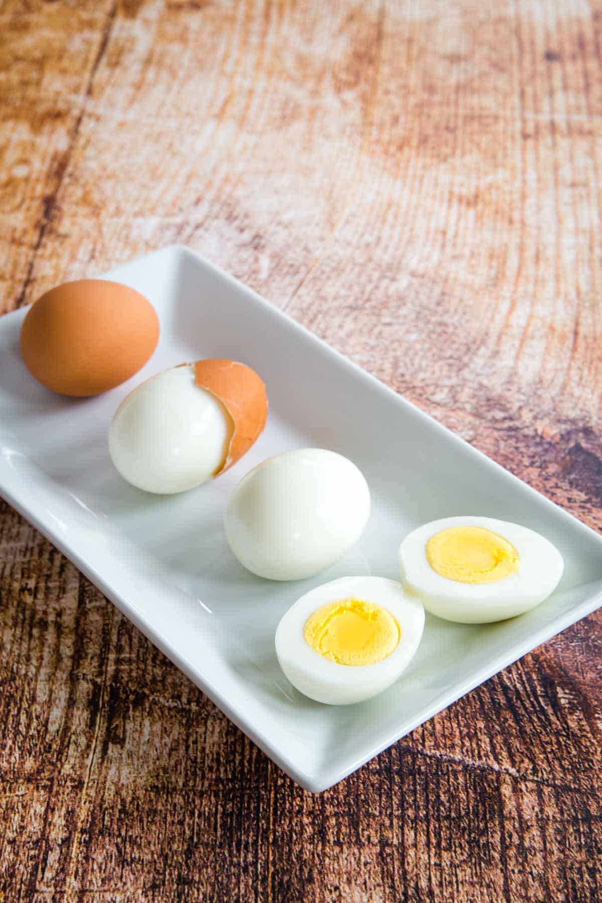 four hard boiled eggs on a plate, one in the shell, one partially peeled, one peeled, and one peeled and cut in half