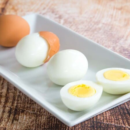 a rectangular white plate with one hard boiled egg in the shell, one with the shell cracked and partially removed, one peeled, and one peeled and cut in half