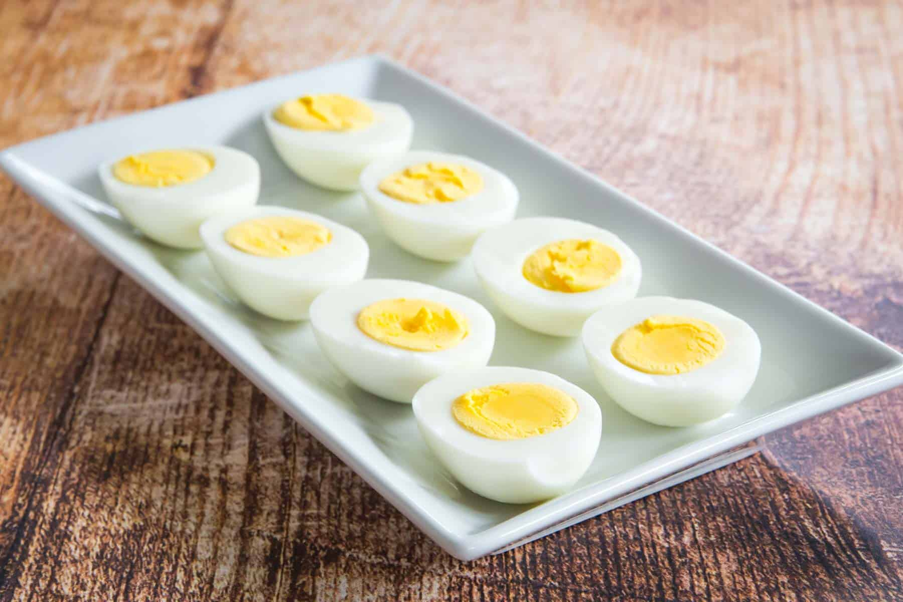 eight halves of hard boiled eggs lined up on a white rectangular plate