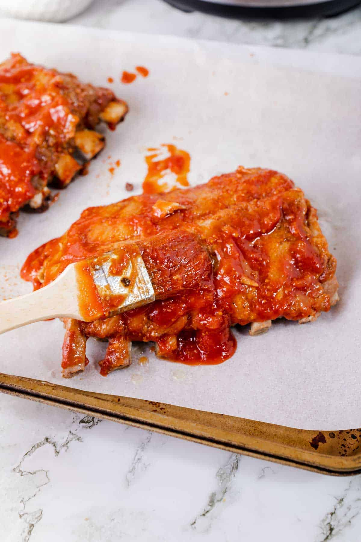 Instant Pot Ribs Being Brushed with Honey Barbecue Sauce