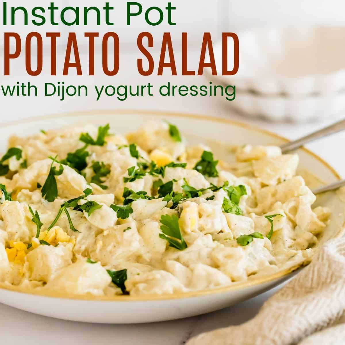 serving bowl of potato salad with two spoons in it