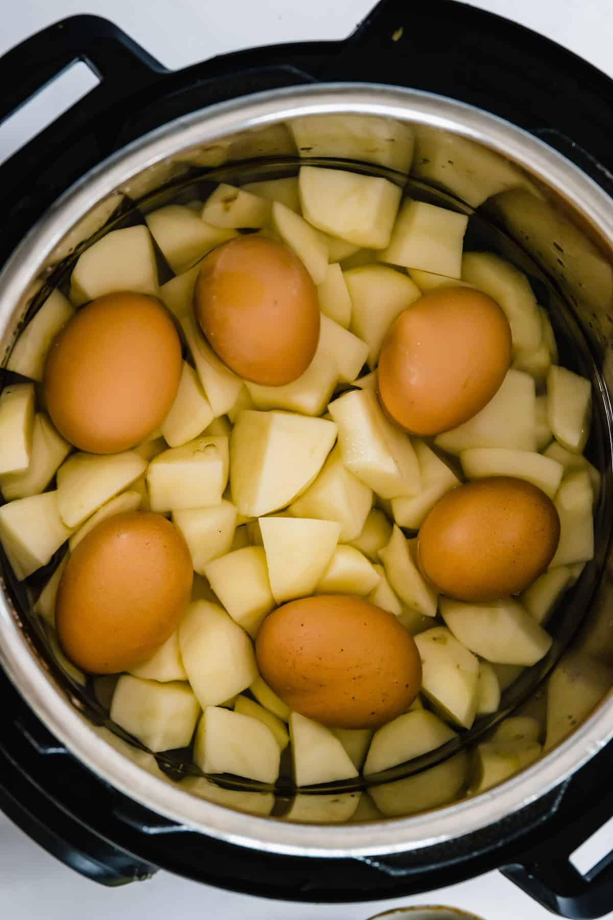 Peeled and Chopped Potatoes in an Instant Pot with Six Eggs on Top
