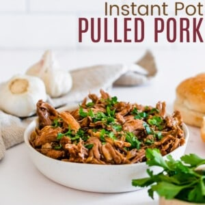 bbq pulled pork in a serving bowl with buns beside it to make barbecue pork sandwiches
