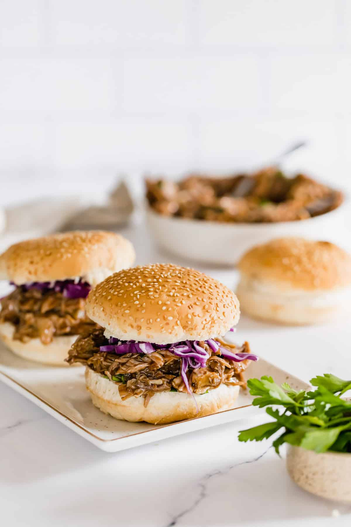 A Platter Holding Two Pulled Pork Sandwiches with a Bowl of Pulled Pork and a Bun in the Background