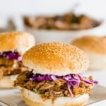 bbq pork sandwich on a sesame seed roll with a bit of red cabbage slaw