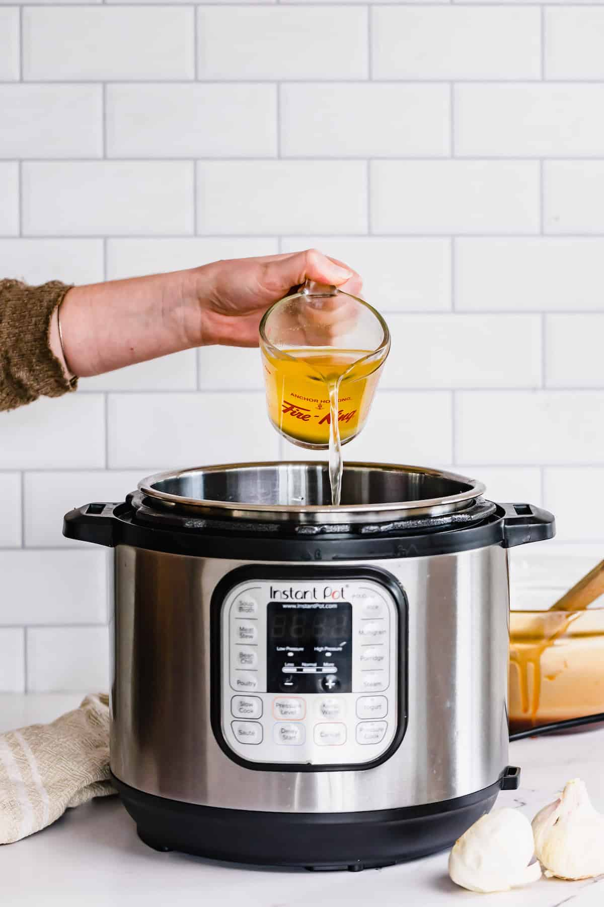 Chicken Broth Being Poured Into the Inner Pot of an Instant Pot