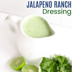 container of jalapeno ranch dressing with cilantro and lime halves next to it