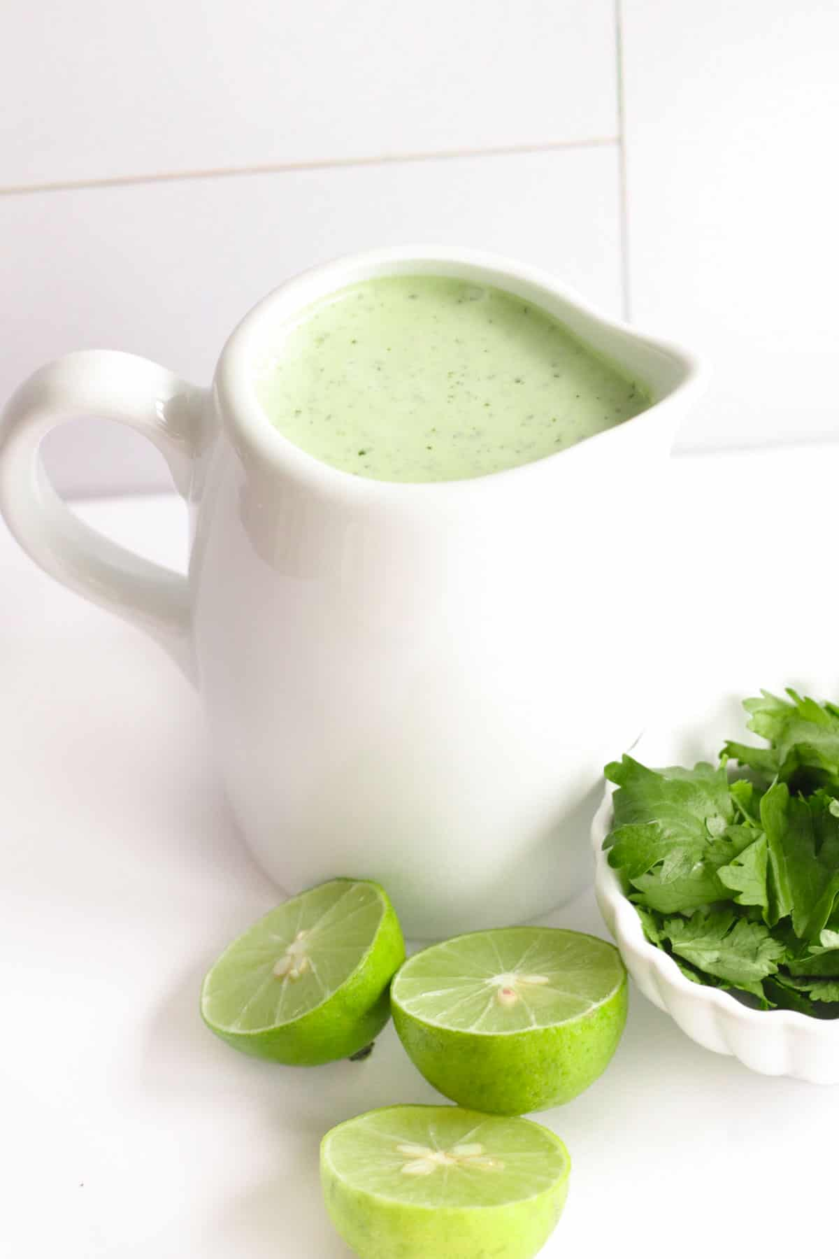 small white pitcher of cilantro lime dressing with limes and cilantro on the table