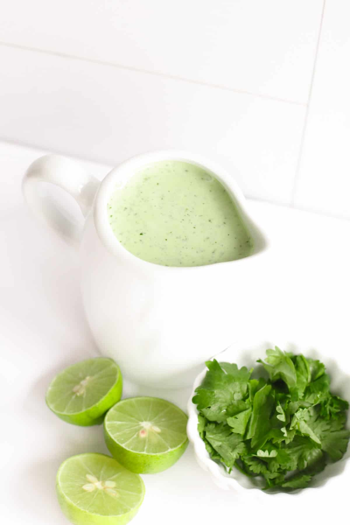 a container of cilantro lime jalapeno ranch salad dressing with a bowl of cilantro and lime halves next to it on a table