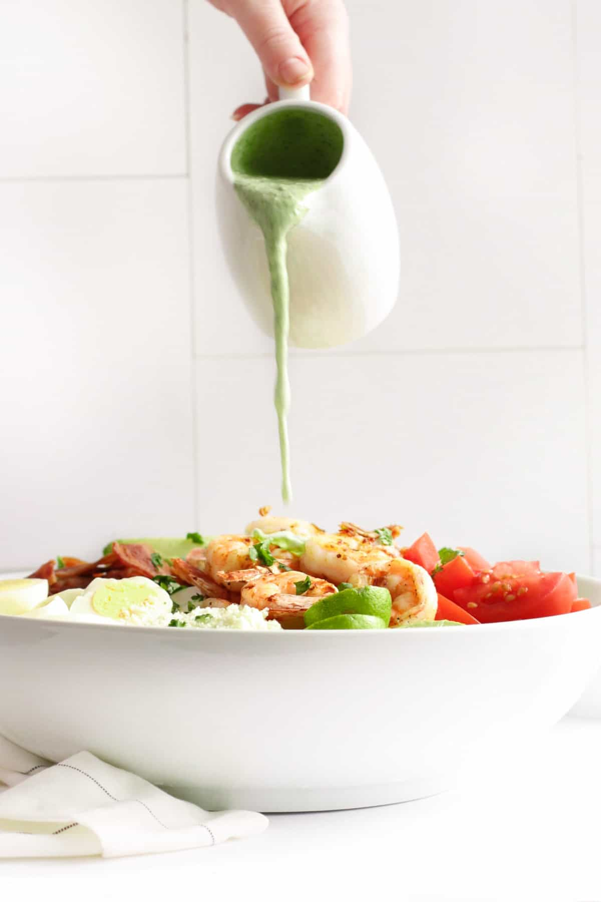 pouring jalapeno ranch dressing over a salad topped with shrimp, tomatoes, eggs, and bacon