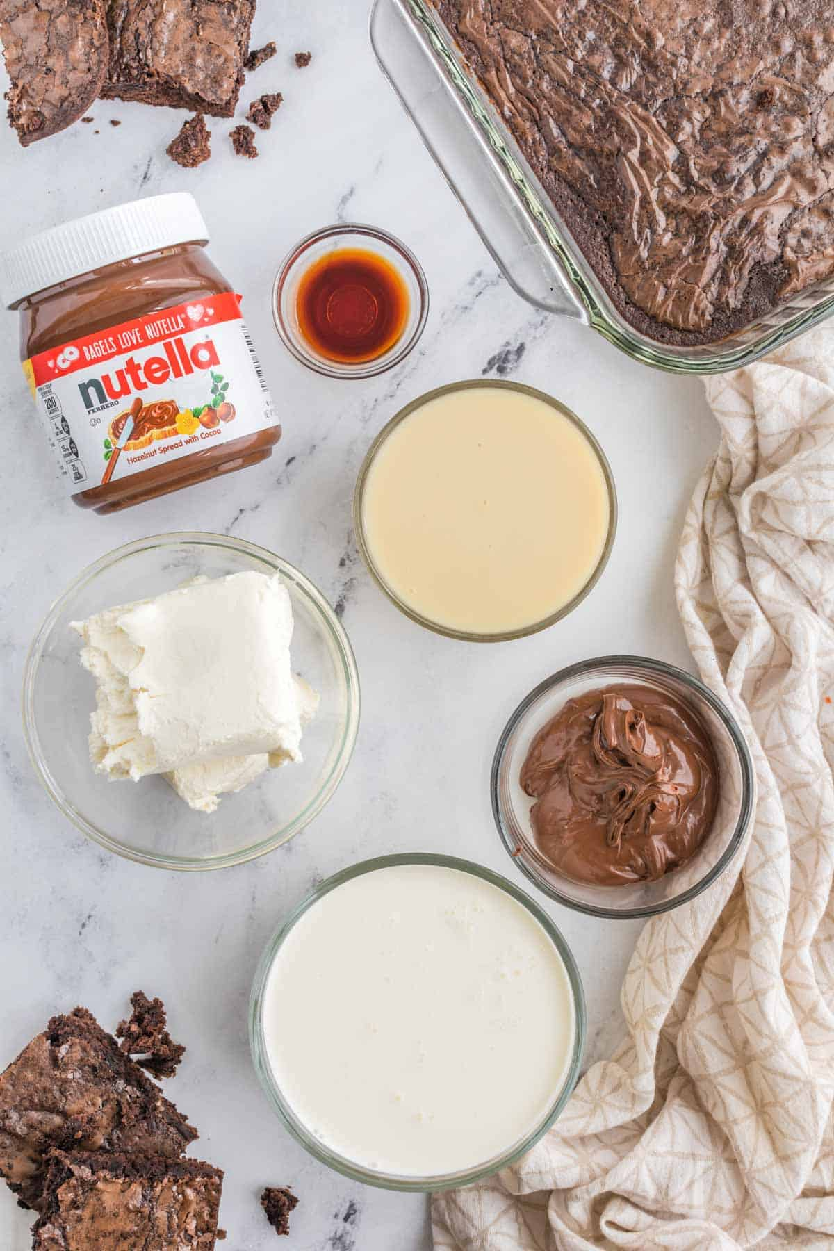 bowls of heavy cream, sweetened condense milk, cream cheese, and vanilla extract and a pan of and pieces of brownies on a marble countertop