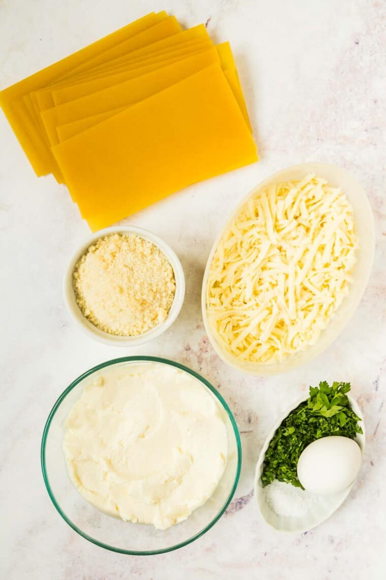 uncooked lasagna noodles, an egg, plus bowls of ricotta cheese, mozzarella, parmesan cheese, and minced parsley on a marble tabletop