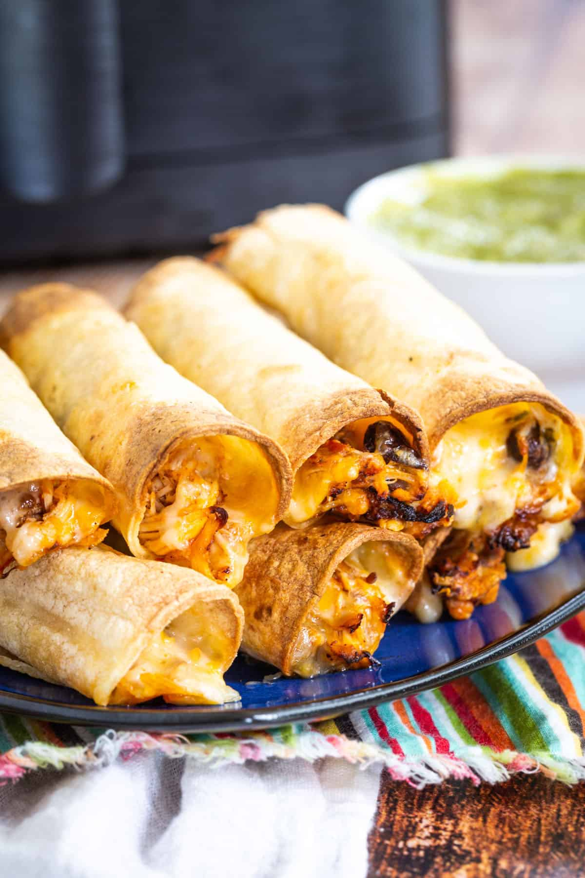 cheesy chicken taquitos stacked on a bleu plate in front of an air fryer and a small bowl of guacamole