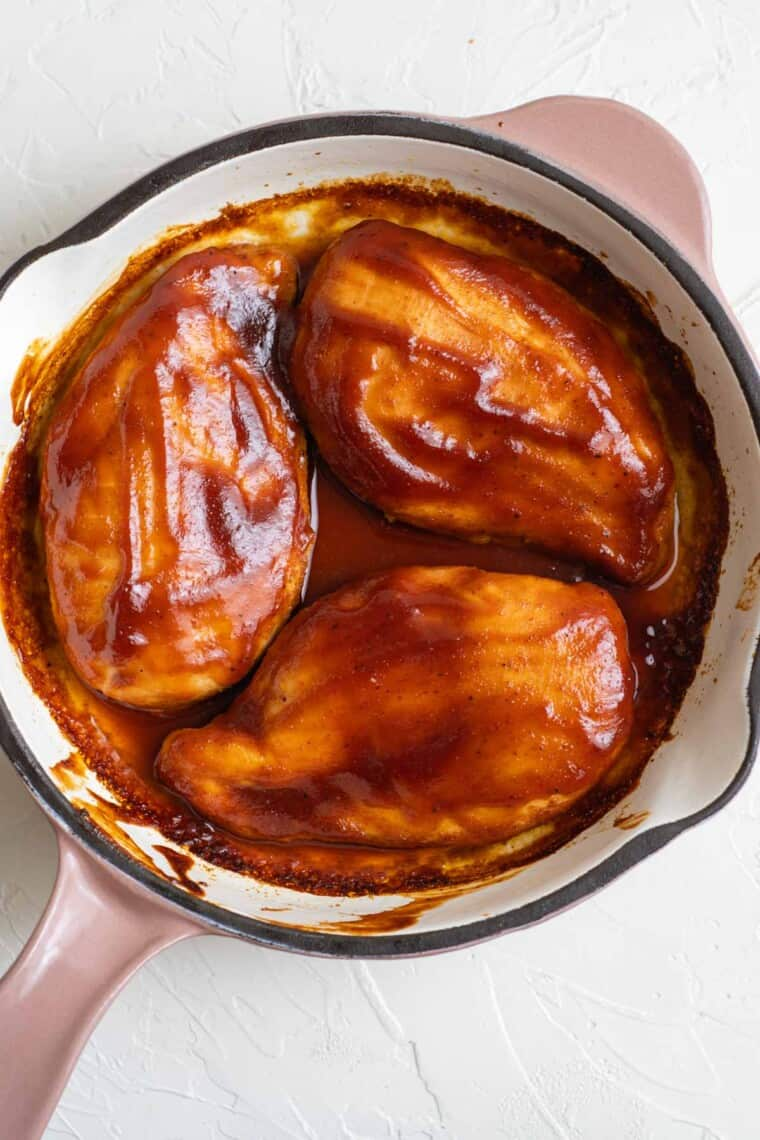 chicken breasts in a skillet covered with barbecue sauce