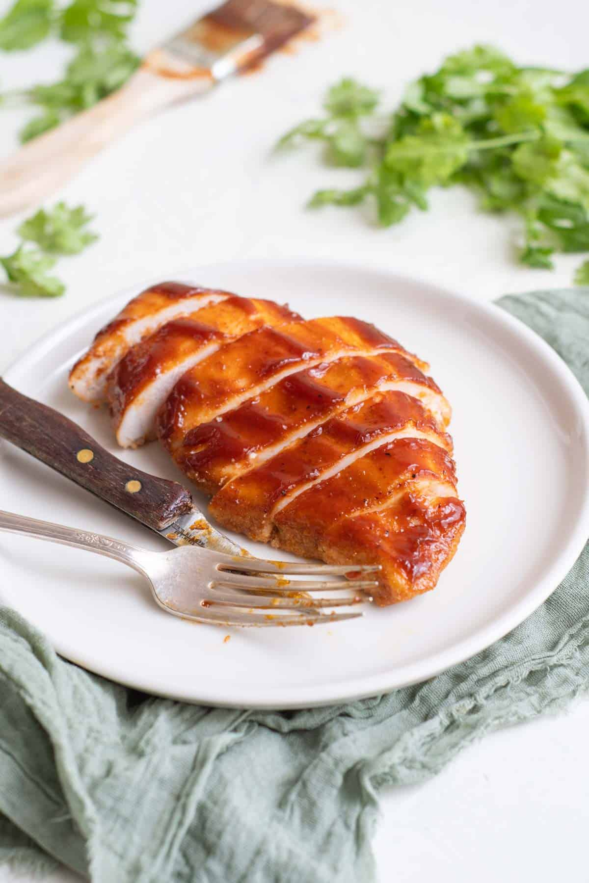 bbq chicken breast on a white plate with a fork and a knife