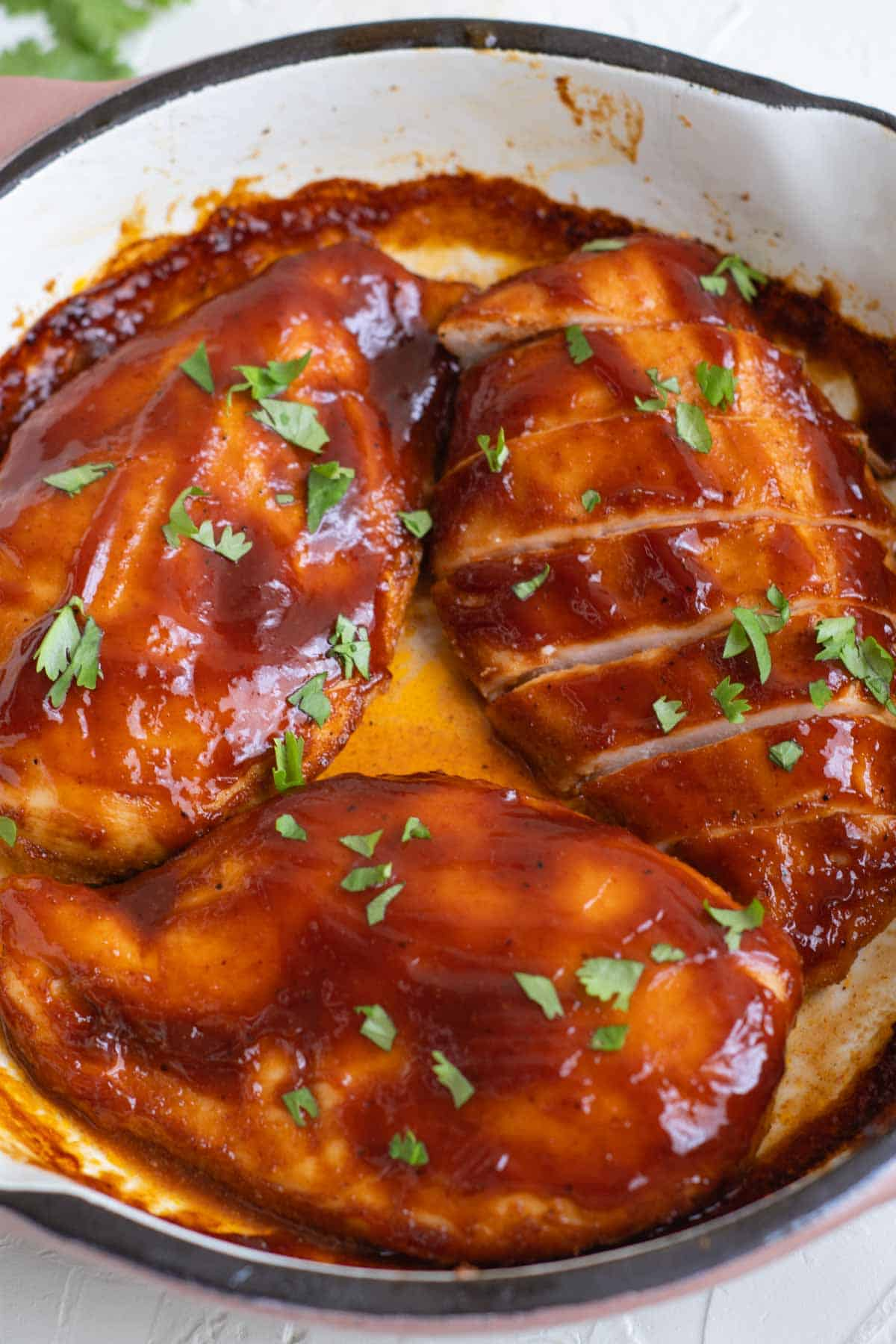 three baked bbq chicken breasts in a skillet with one sliced