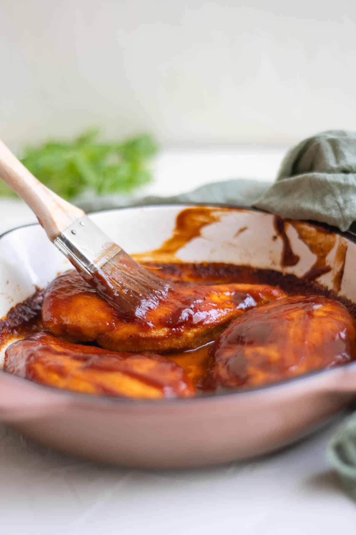 pastry brush brushing barbecue sauce onto chicken breasts in a skillet