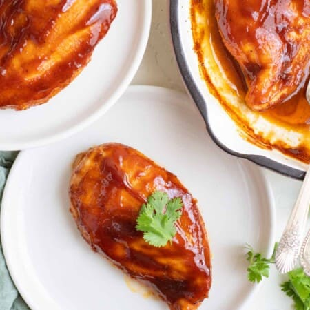 two white plates each with a barbecue chicken breast with one more in a skillet