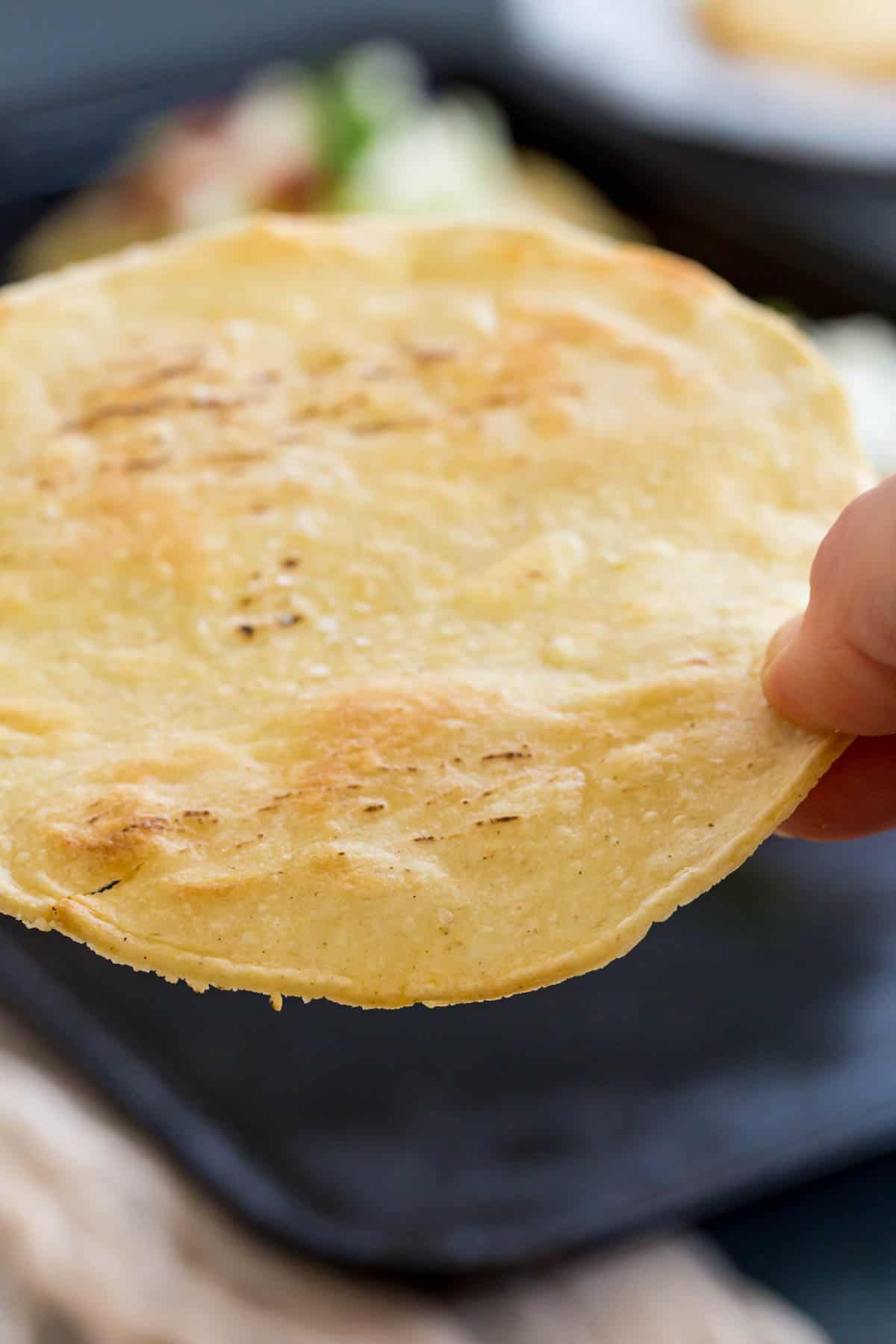picking up a tostada shell off of a baking pan