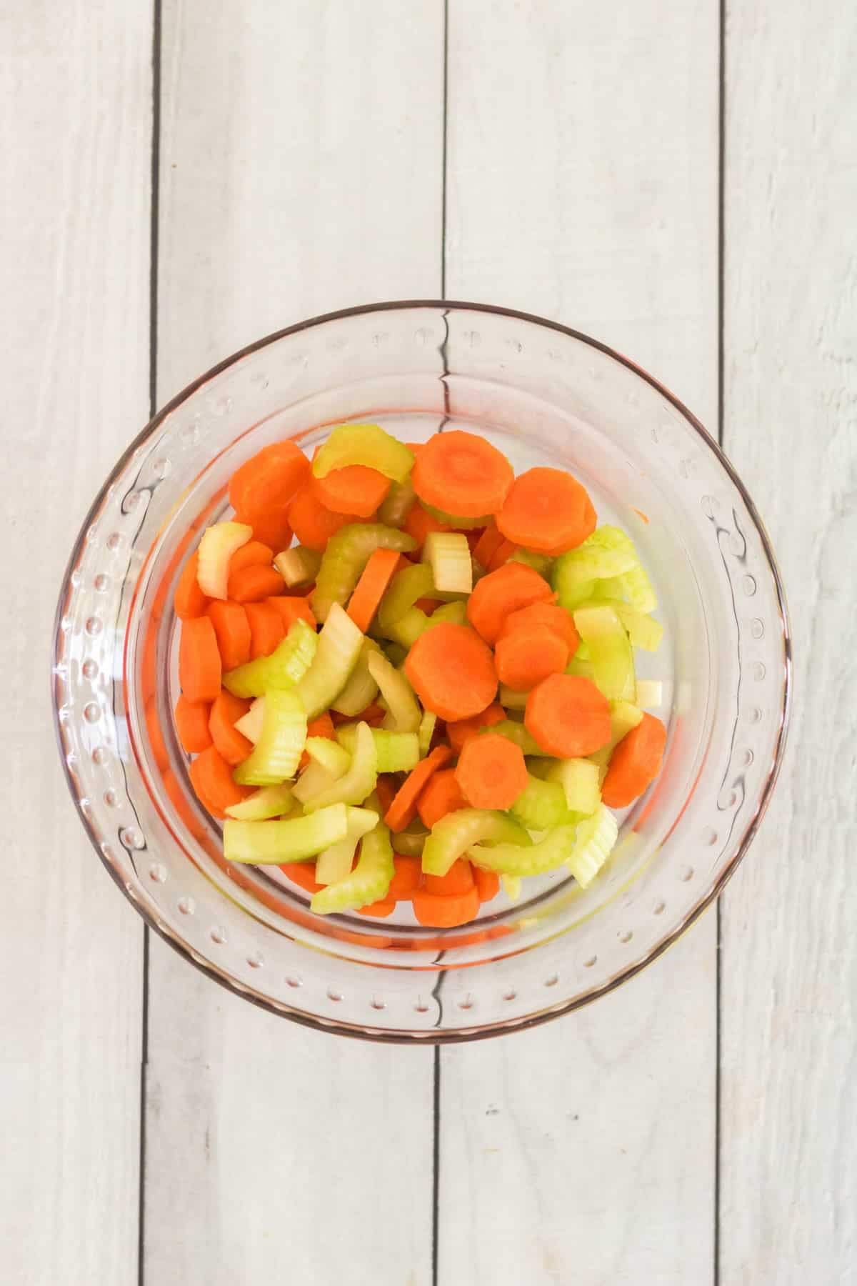 glass bowl with sliced carrots and celery