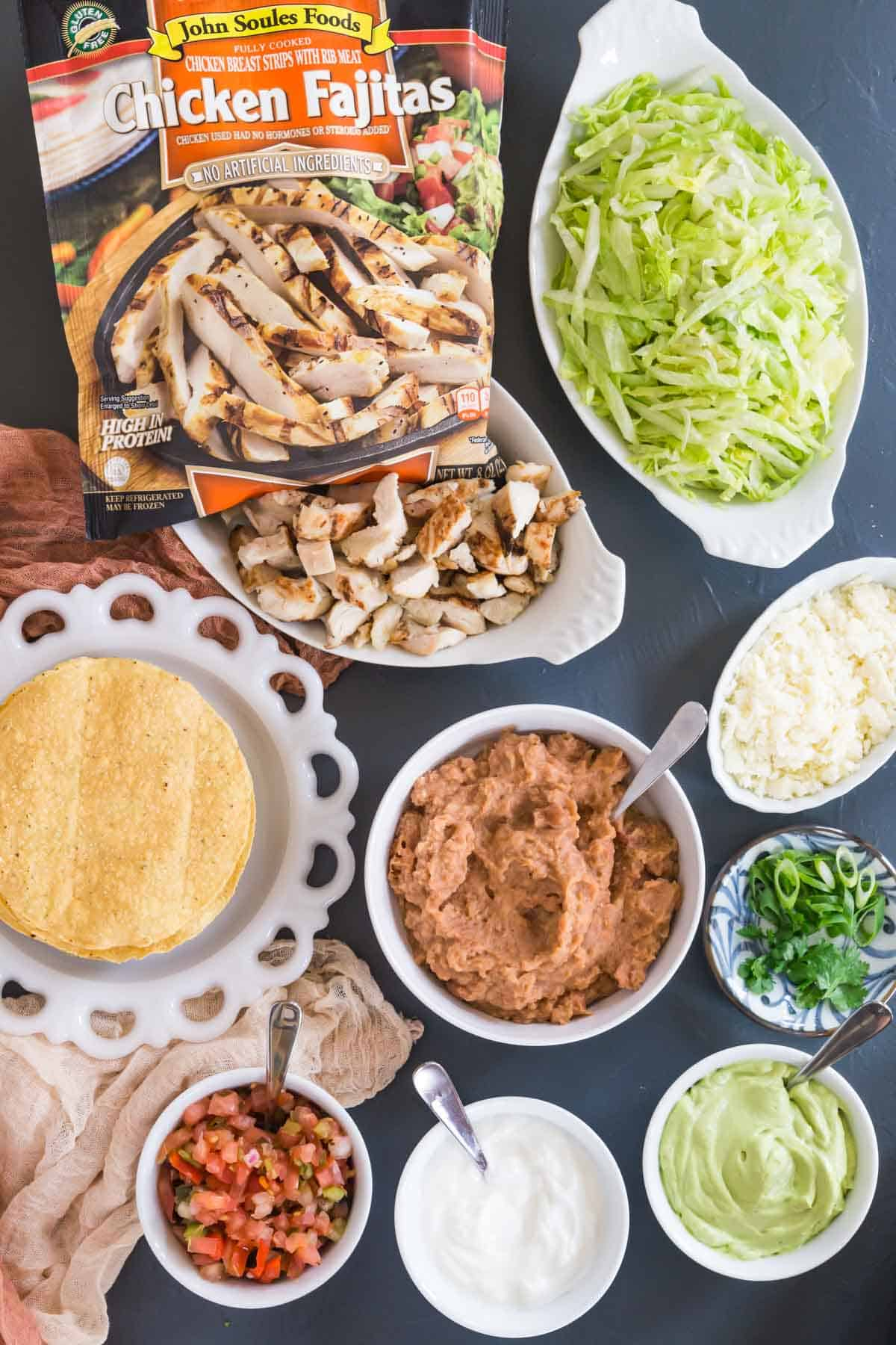 a plate of tostada shells with bowls of fully cooked chicken strips, lettuce, crumble cotija cheese, refried beans, salsa, sour cream, guacamole, and cilantro and scallions