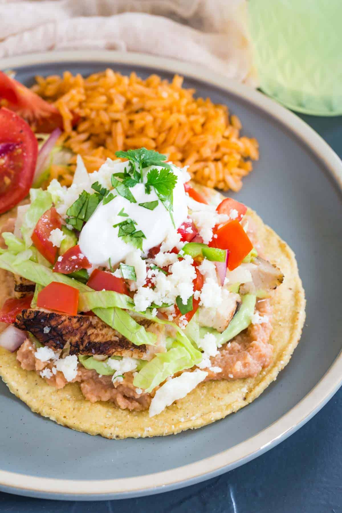 a chicken tostada with refried beans, lettuce, salsa, cheese, and sour cream served on a blue plate with mexican rice