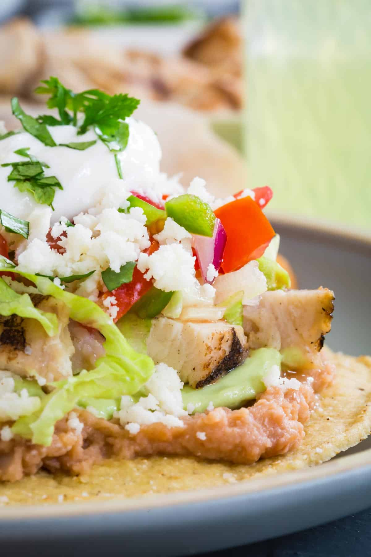 a crispy corn tortilla topped with layers of refried bans, guacamole, cooked chicken pieces, lettuce, salsa, crumbled cotija cheese, sour cream and a garnish of cilantro