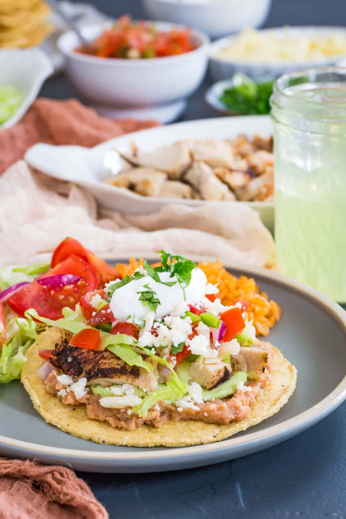 a chicken tostada on a plate with rice and bowls of all of the toppings in the background