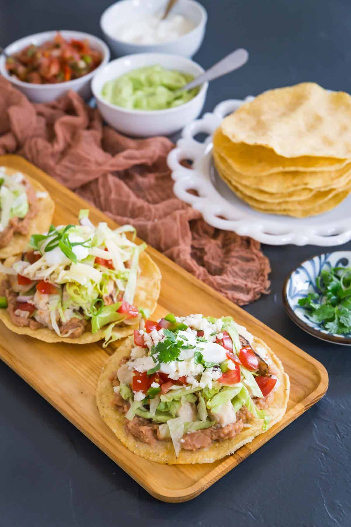 three chicken tostadas on a wooden serving platter with a plate of tostada shells and bowls of salsa, sour cream, and guacamole