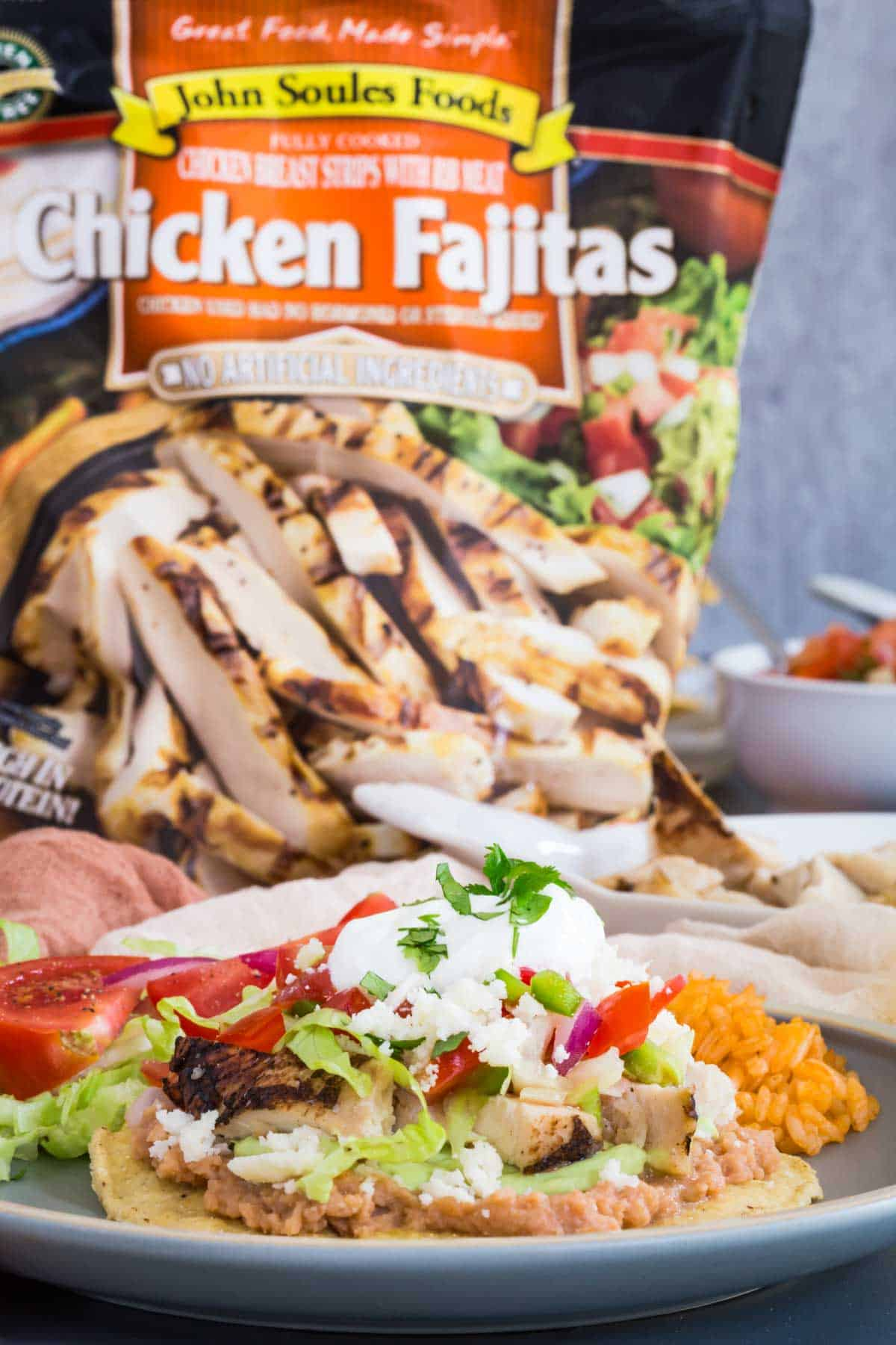 a chicken tostada on a plate with a bag of John Soules Foods fully cooked chicken fajita strips behind it