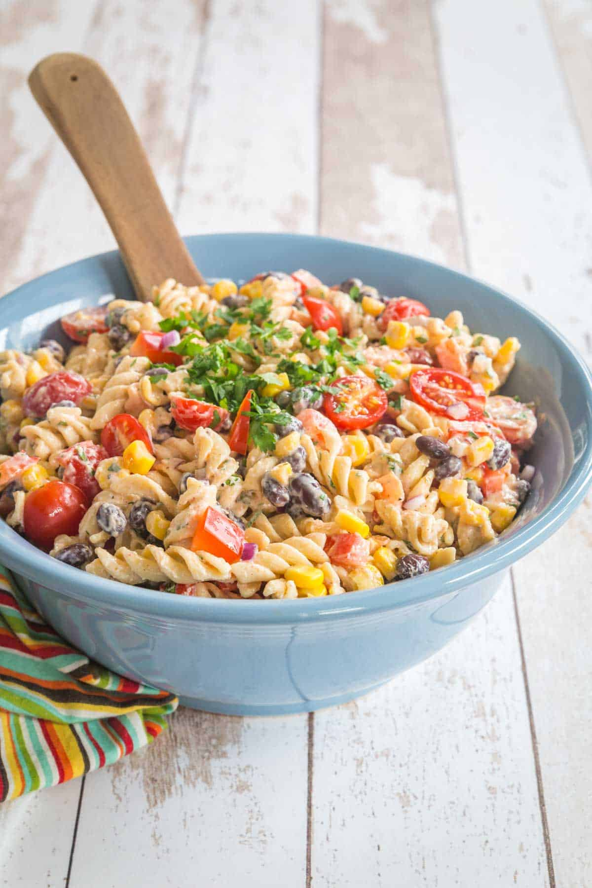creamy southwestern pasta salad in a blue serving bowl on top of a multicolored striped napkin