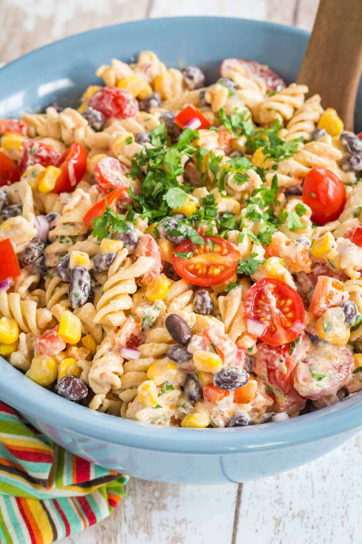 blue serving bowl of mexican pasta salad with creamy southwestern dressing with a wooden serving spoon