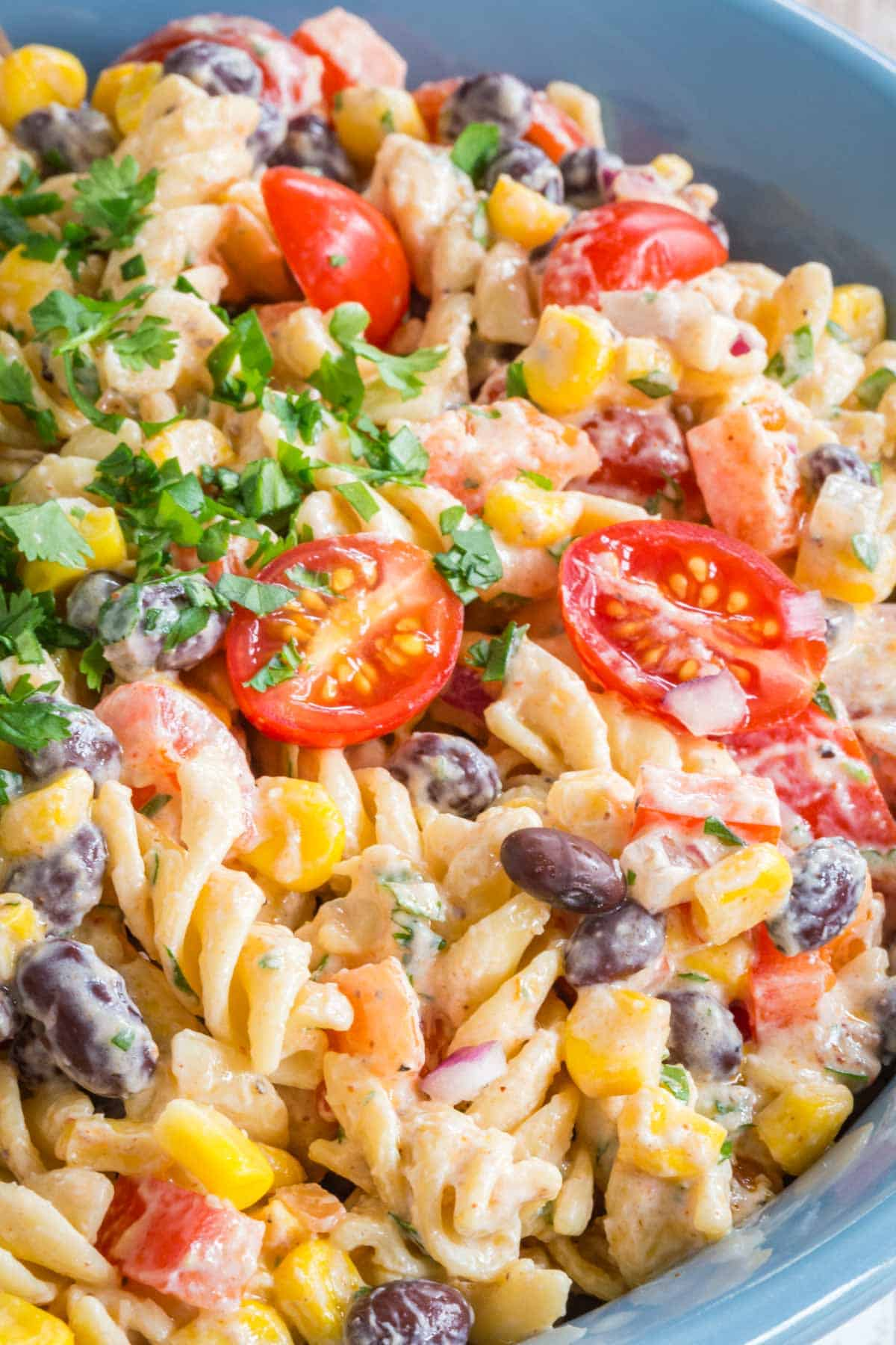closeup of the rotini pasta, black beans, corn, peppers, tomatoes, and red onions coated in a creamy dressing with a garnish of cilantro