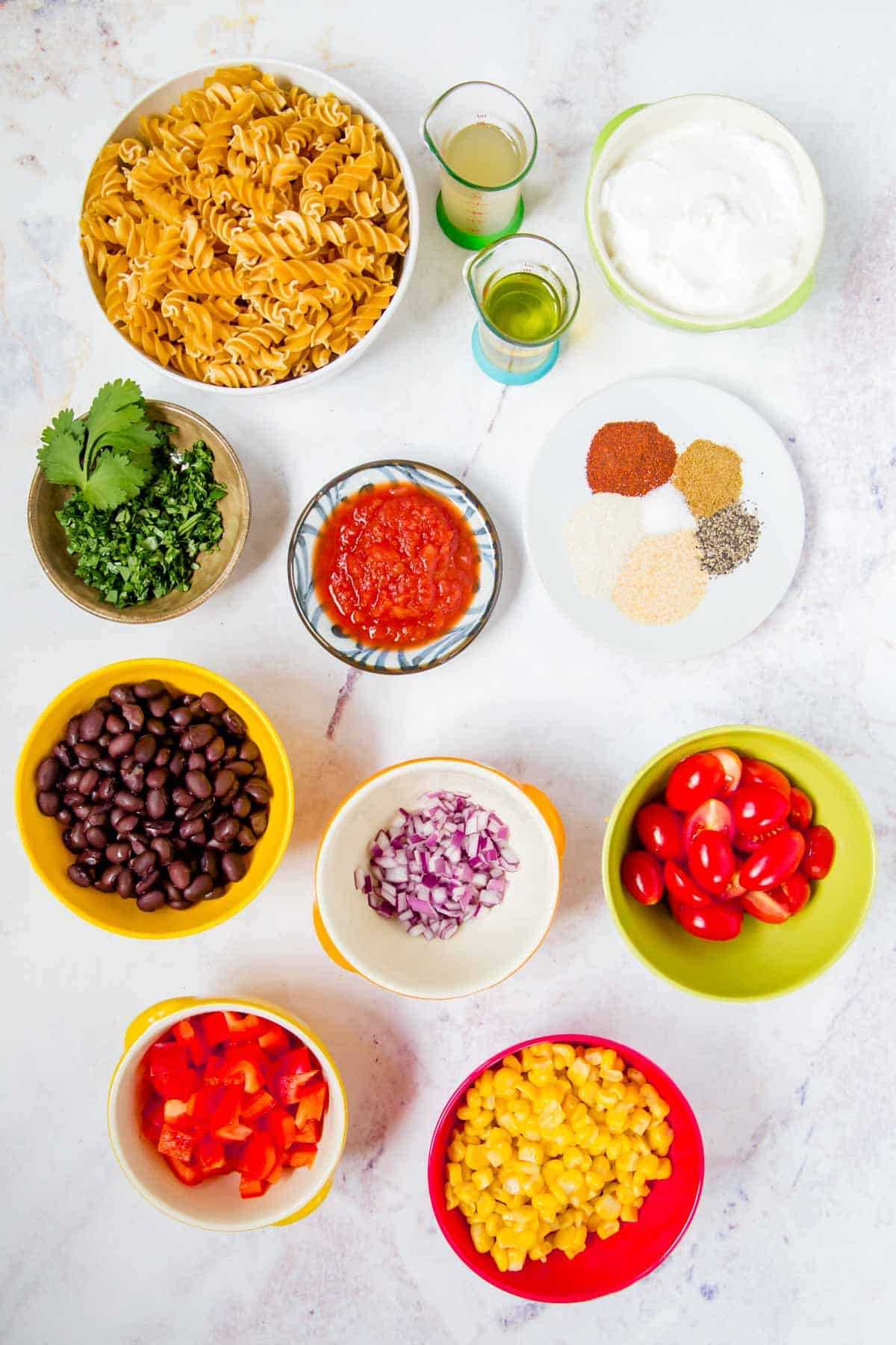 bowls of uncooked pasta, corn, black beans, chopped red pepper, halved grape tomatoes, minced red onion, greek yogurt, salsa, and cilantro, olive oil and vinegar in small measuring beakers, and a plate with spices
