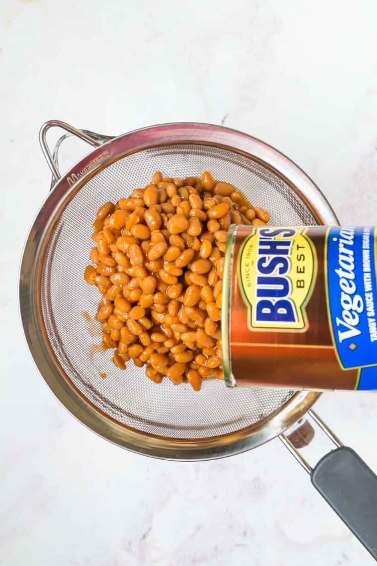pouring a can of Bush's baked beans into a wire strainer set over a glass bowl