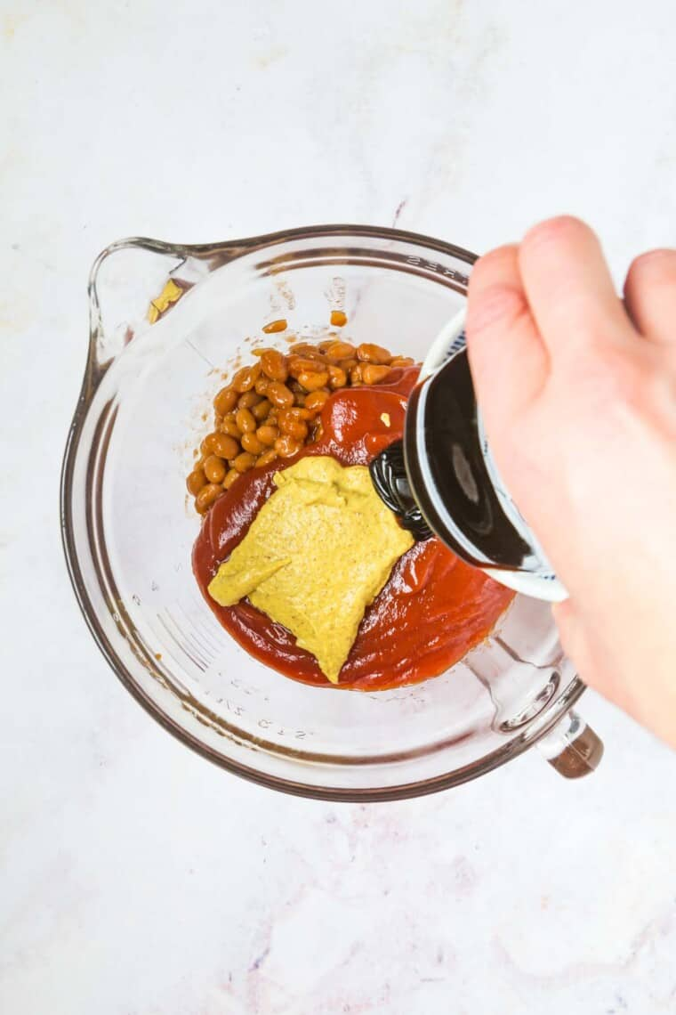 pouring molasses into the bowl with the drained beans, ketchup, and mustard
