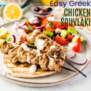 two chicken kabobs over pita drizzled with tzatziki sauce and served on a plate with Greek salad