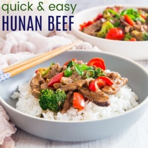 hunan beef in a bowl with white rice and chopsticks balanced on the side of the dish