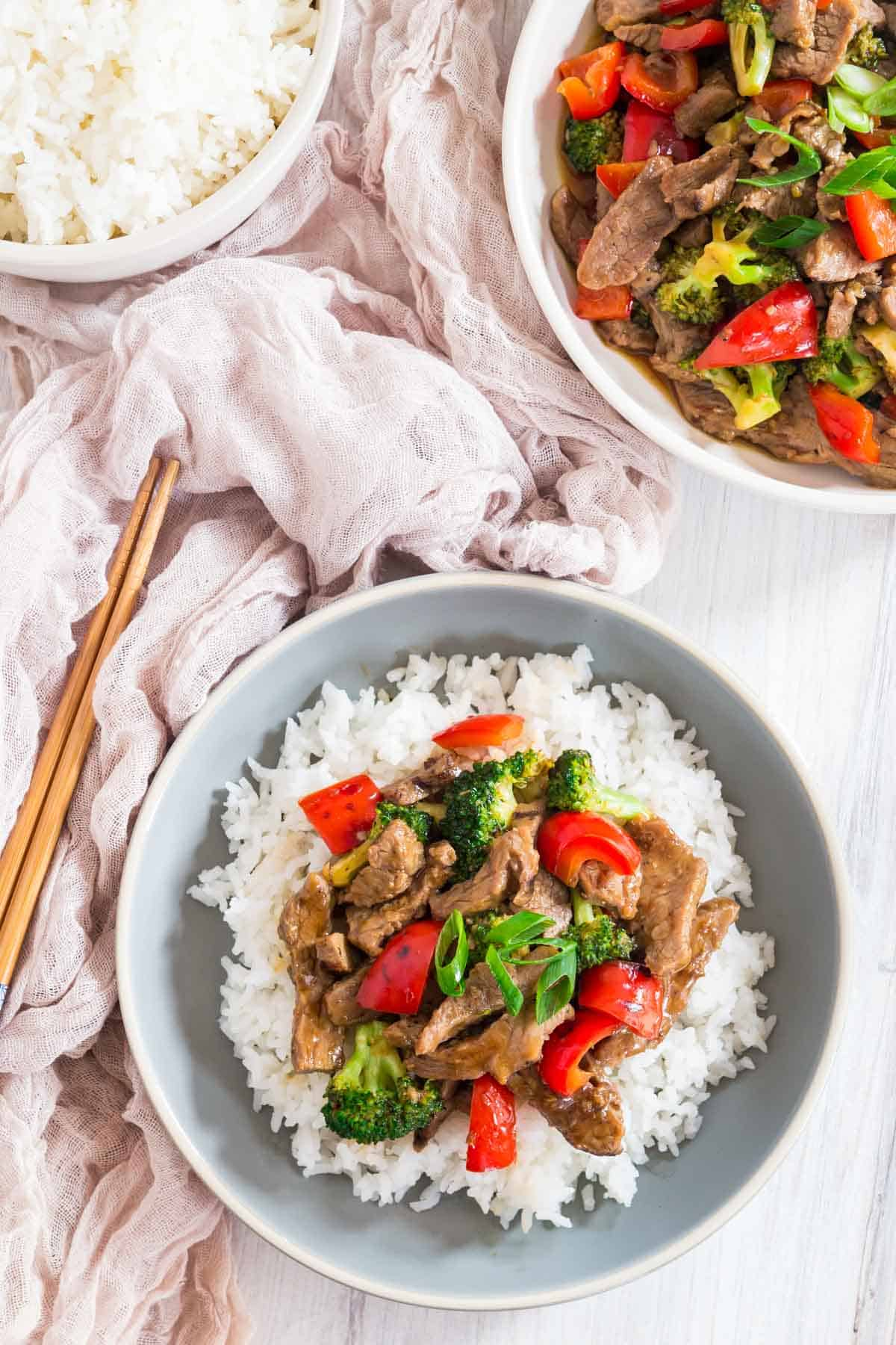 hunan beef with rice in a bowl with chopsticks alongside and separate bowls of the stir fry and white rice